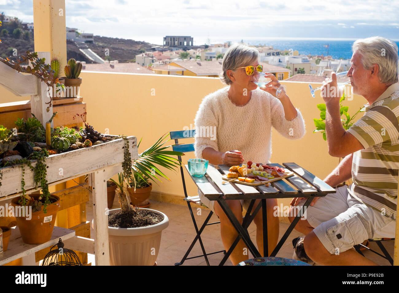 Beau couple de retraités des profils rester ensemble sur le roofto pterrace boire et manger certains aliments et boissons. sourire heureux les gens en plein air grand lifesty Photo Stock