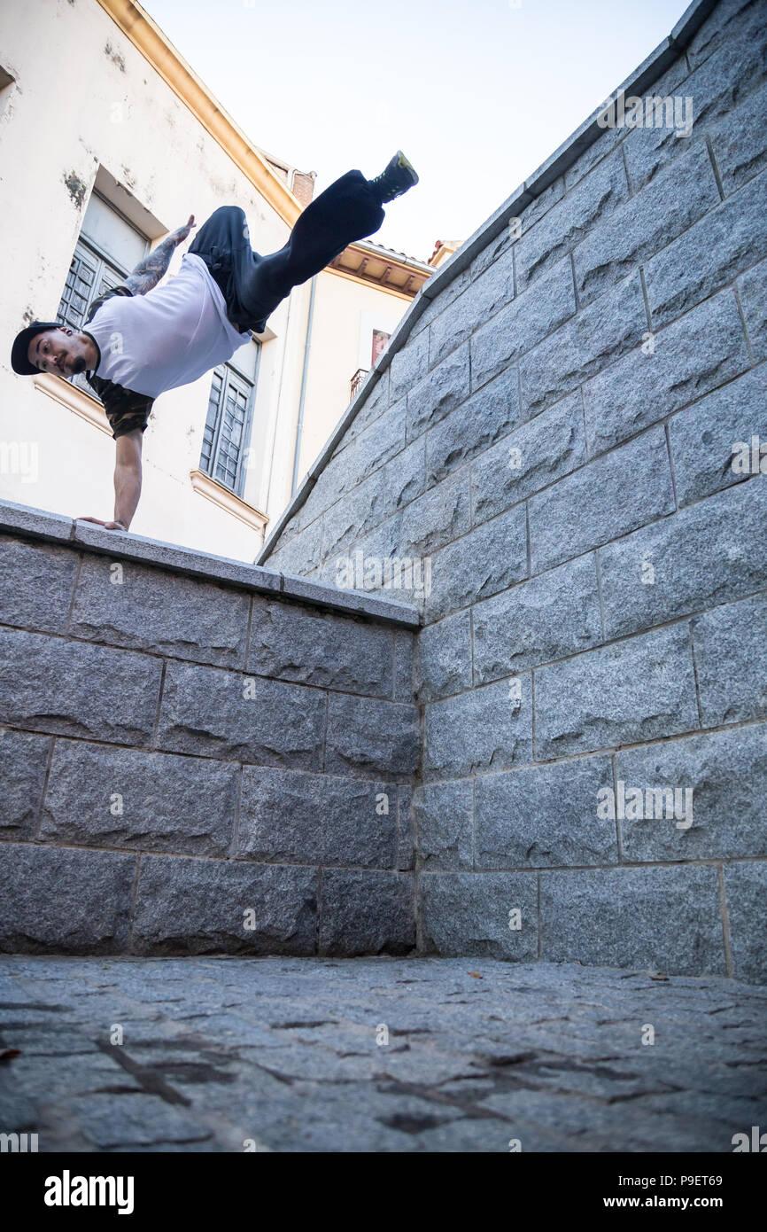 Jeune homme faisant un incroyable tour de parkour dans la rue. Photo Stock