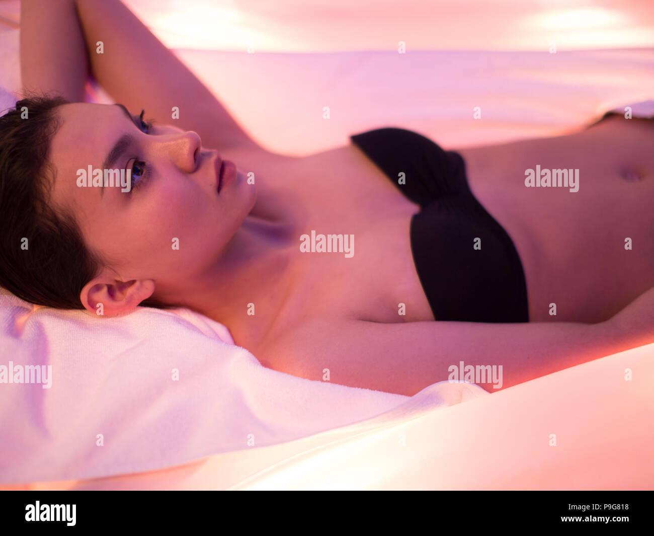 Fille asiatique agréable couché sur le massage avec les technologies modernes Photo Stock