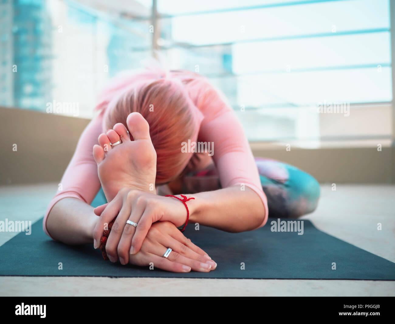Jeune femme mince avec des cheveux teints en rose faisant du yoga pratique sur terrasse de ville moderne. Maintien de la jeune fille en bonne santé et détente sur le corps pendant la pratique sur le toit Poser Photo Stock