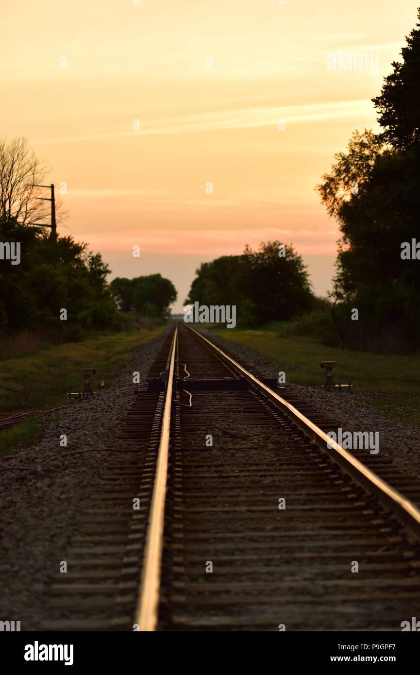 Burlington, Vermont, USA. Voie ferrée jusqu'à l'horizon et le ciel par une récente inflammées coucher du soleil dans les régions rurales de l'Illinois. northesatern Photo Stock
