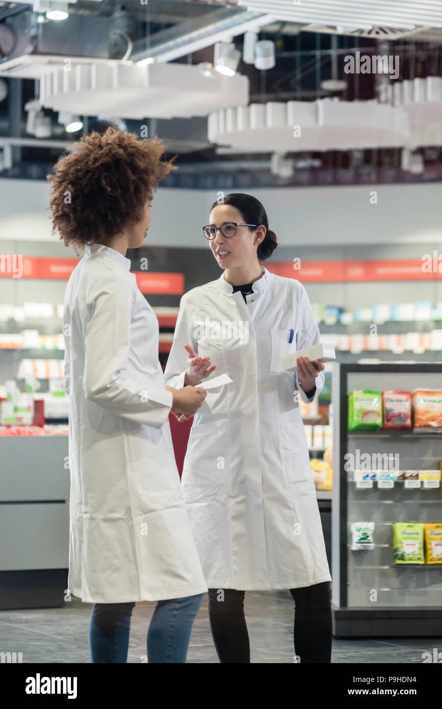 Deux collègues de parler tout en travaillant ensemble que les pharmaciens Photo Stock