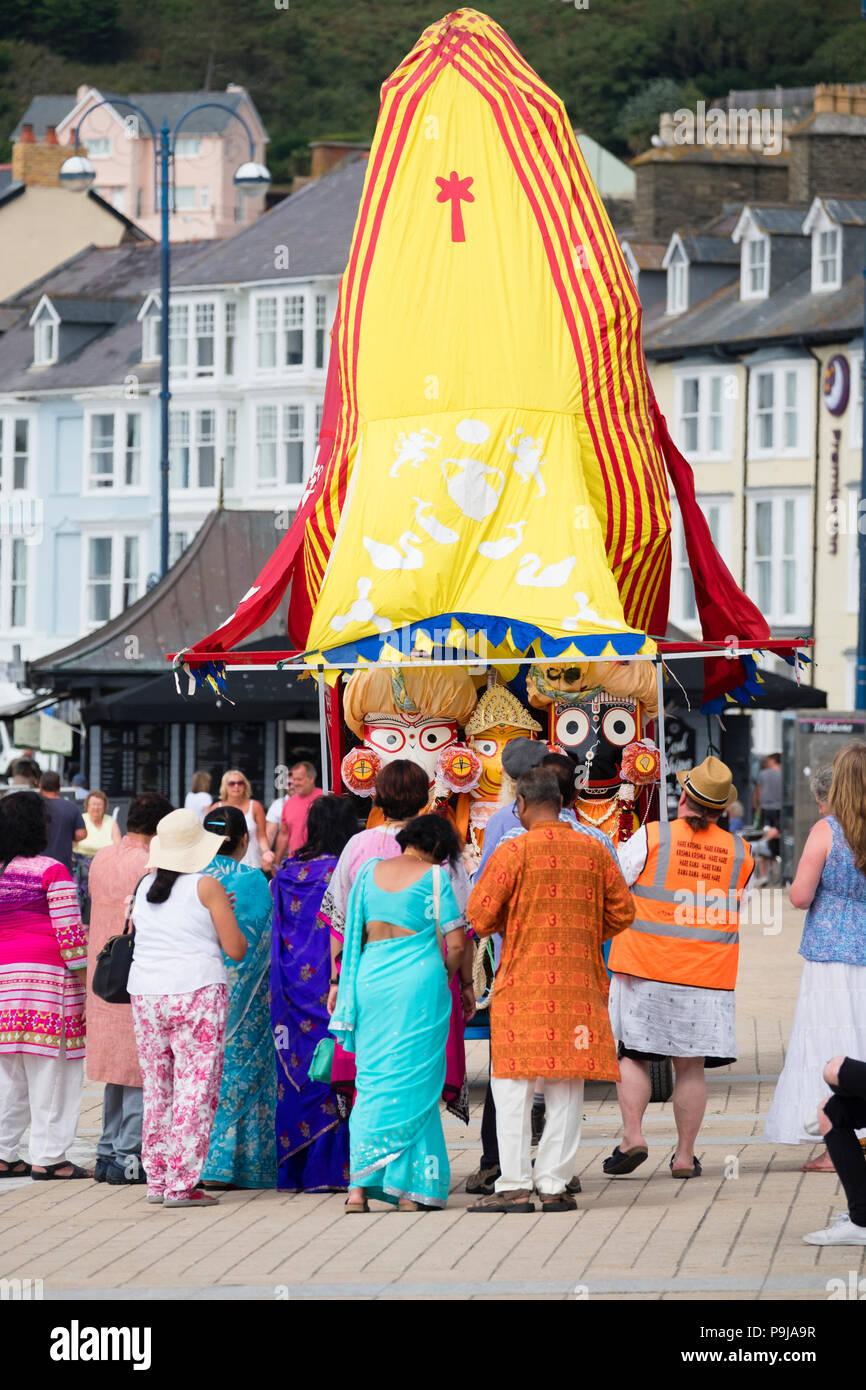 """La foi et la religion sur le Royaume-uni: un groupe de dévots Hare Krishna avec leur """"Ratha' un temple mobile votive char pour la déité Seigneur Jagannath, chantant comme ils le remorquer le long de la promenade à Aberystwyth, Pays de Galles, Royaume-Uni par un après-midi d'été Banque D'Images"""