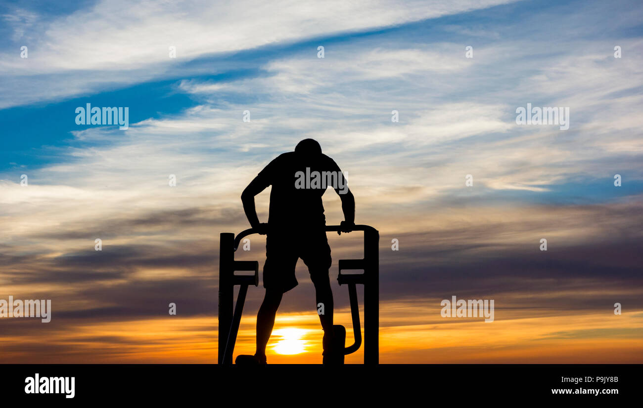 Vue arrière de l'homme à l'aide de machine d'exercice dans la rue de la ville au lever du soleil Photo Stock