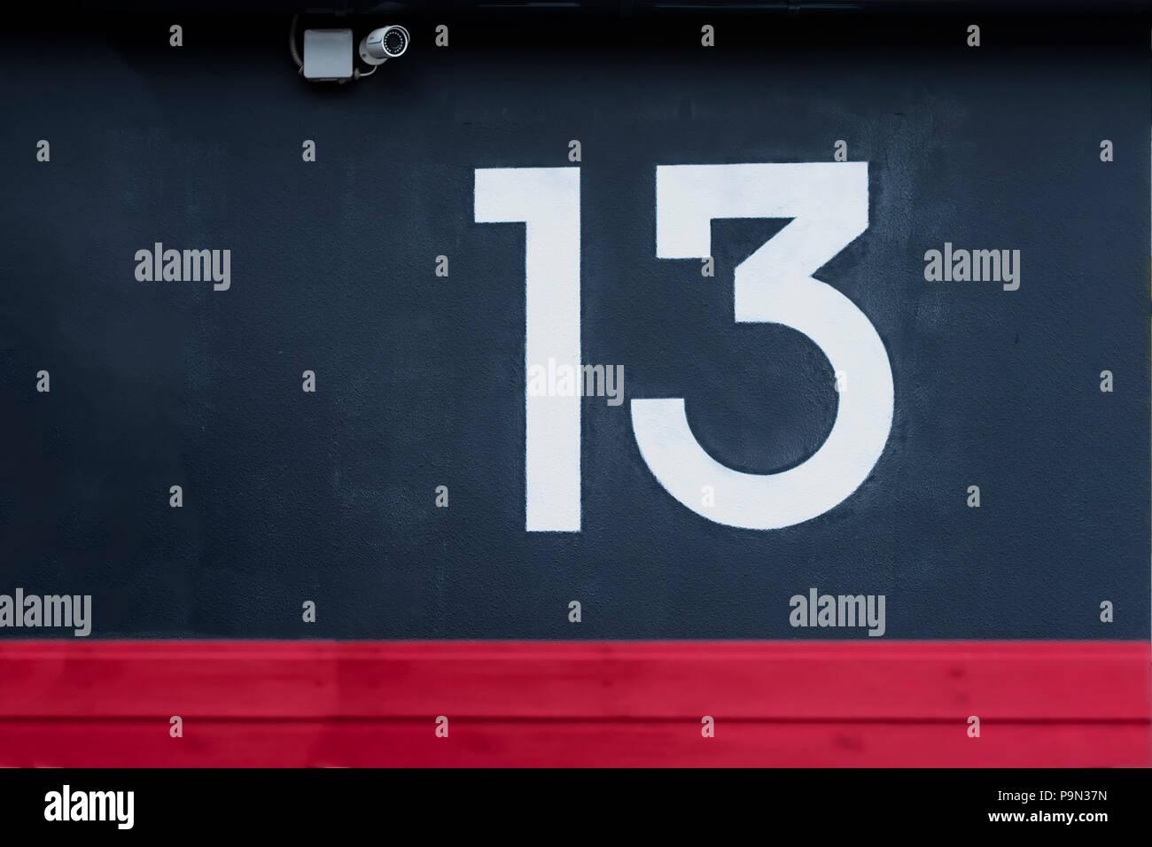 Numéro treize écrites sur le mur de béton Bleu avec caméra surveillance Photo Stock