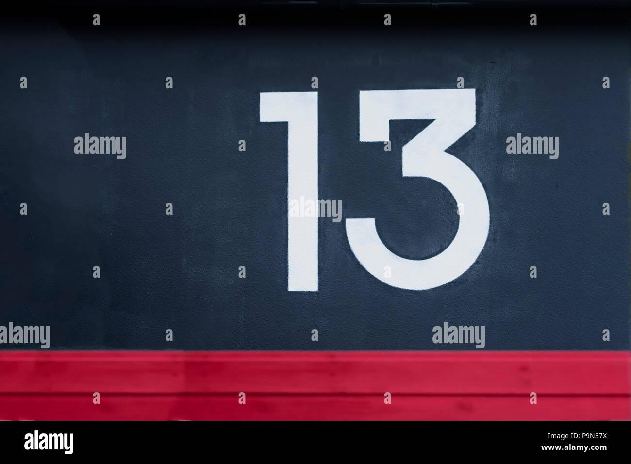 Numéro treize écrites sur le mur de béton rouge bleu Photo Stock
