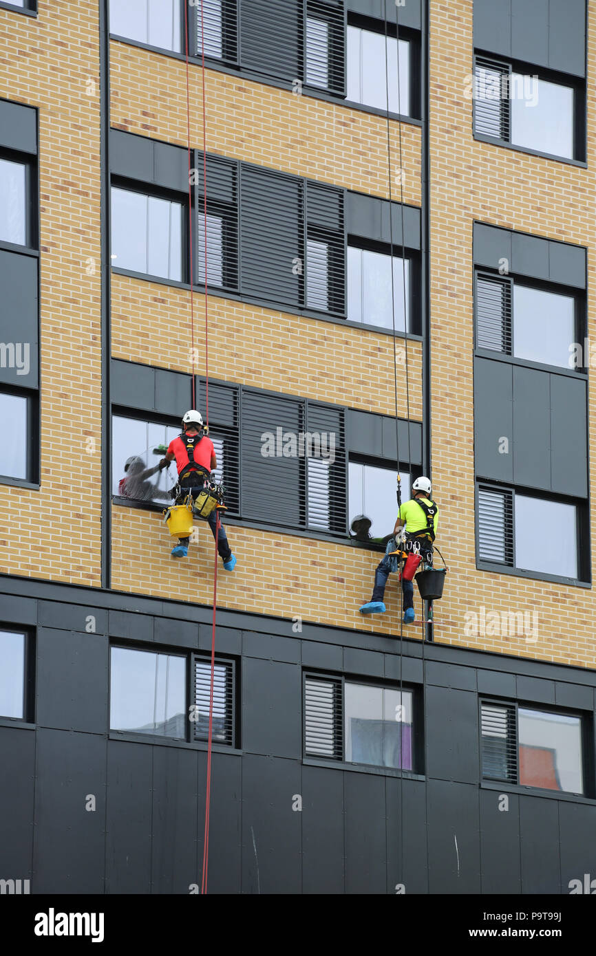 Deux laveurs de vitres de la descente en rappel d'utilisation de cordes pour accéder à Windows sur une nouvelle forme de tour dans le centre-ville de Portsmouth, Hampshire, Royaume-Uni Photo Stock