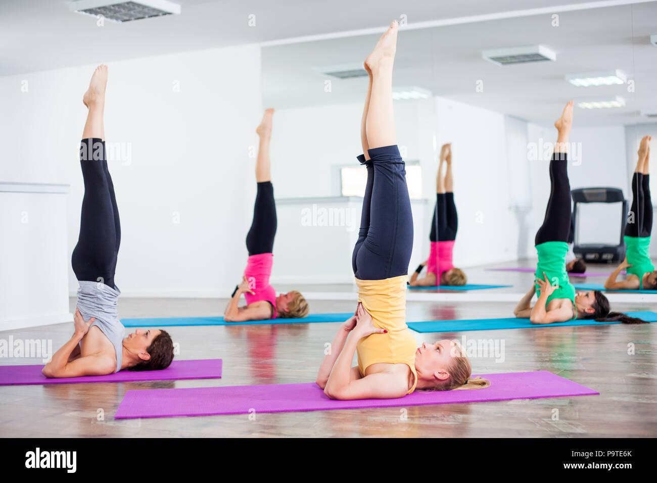 Quatre jeunes filles pratiquant le yoga, Salamba Sarvangasana / stand d'épaule Photo Stock