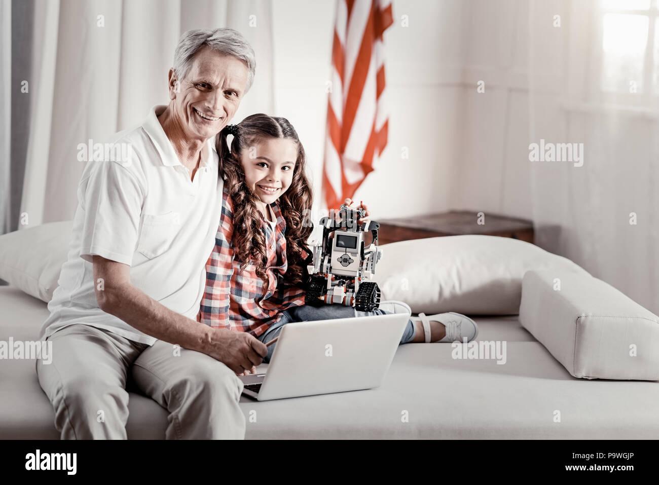 Dépenses de temps ensemble. Joyeux Heureux grand-père insouciant et grandkid souriant pour l'appareil photo alors que girl hugging toy debout sur sa jambe avec une main Photo Stock