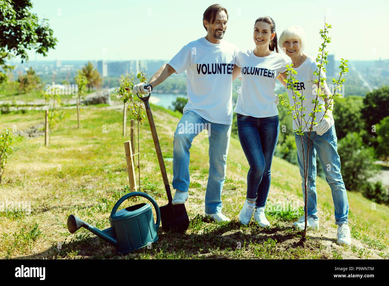 Groupe de volontaires debout près de nouvelles plantes Banque D'Images