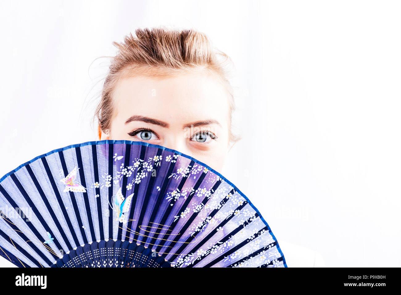 Jeune fille timide, fille avec ventilateur, ventilateur à l'aide de jeune fille, chinois, ventilateur ventilateur ventilateur fixe, rigide, se cachant derrière ventilateur, vue perçante, yeux, jolie yeux, peau, douce, magnifique Photo Stock