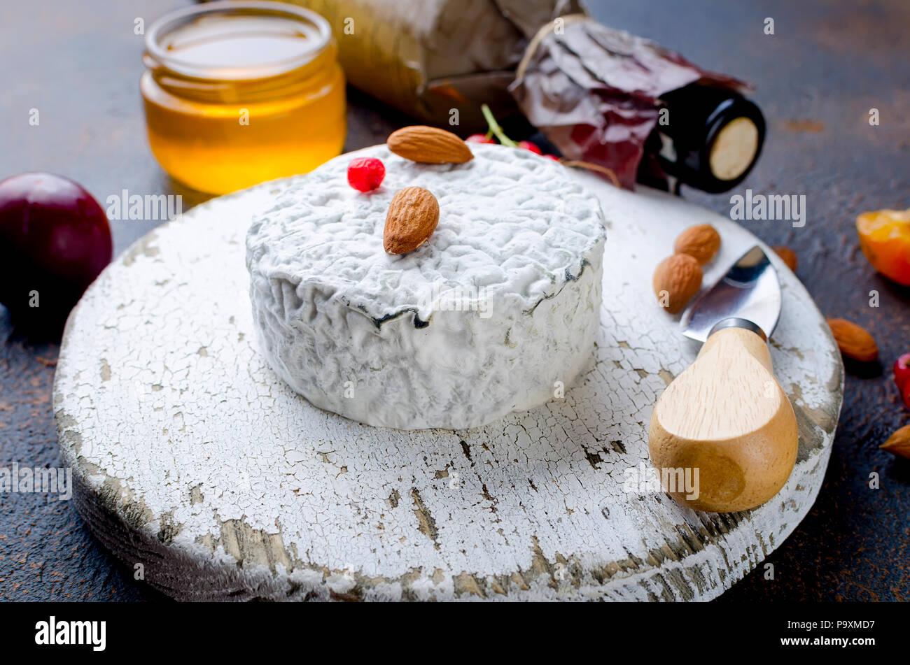 Tête ronde de fromage bleu avec du miel, de cassis, de fruits à coque et une bouteille de vin sur un tableau sombre, concept de gastronomie, fromage italien, romantique ev Photo Stock