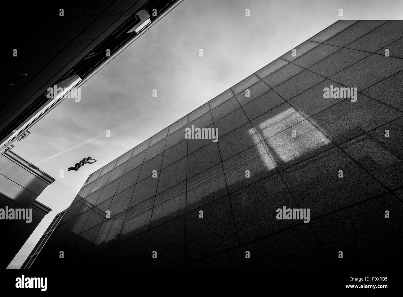 Vue de dessous du parkour masculin athlète sautant d'un toit à un autre Photo Stock