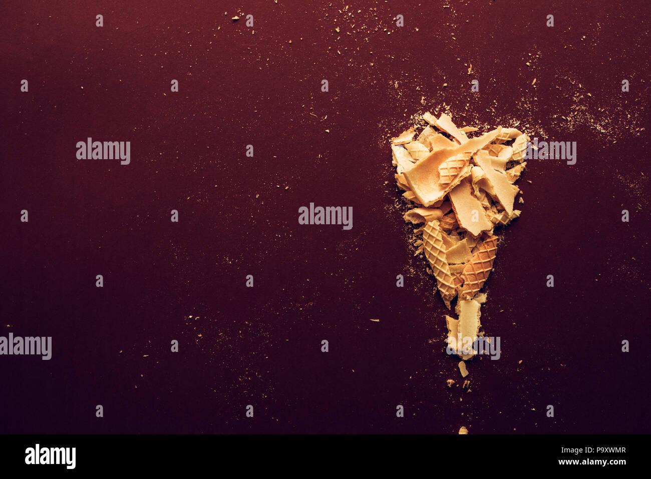 Cornet de crème glacée écrasée sur fond marron foncé, télévision lay Photo Stock