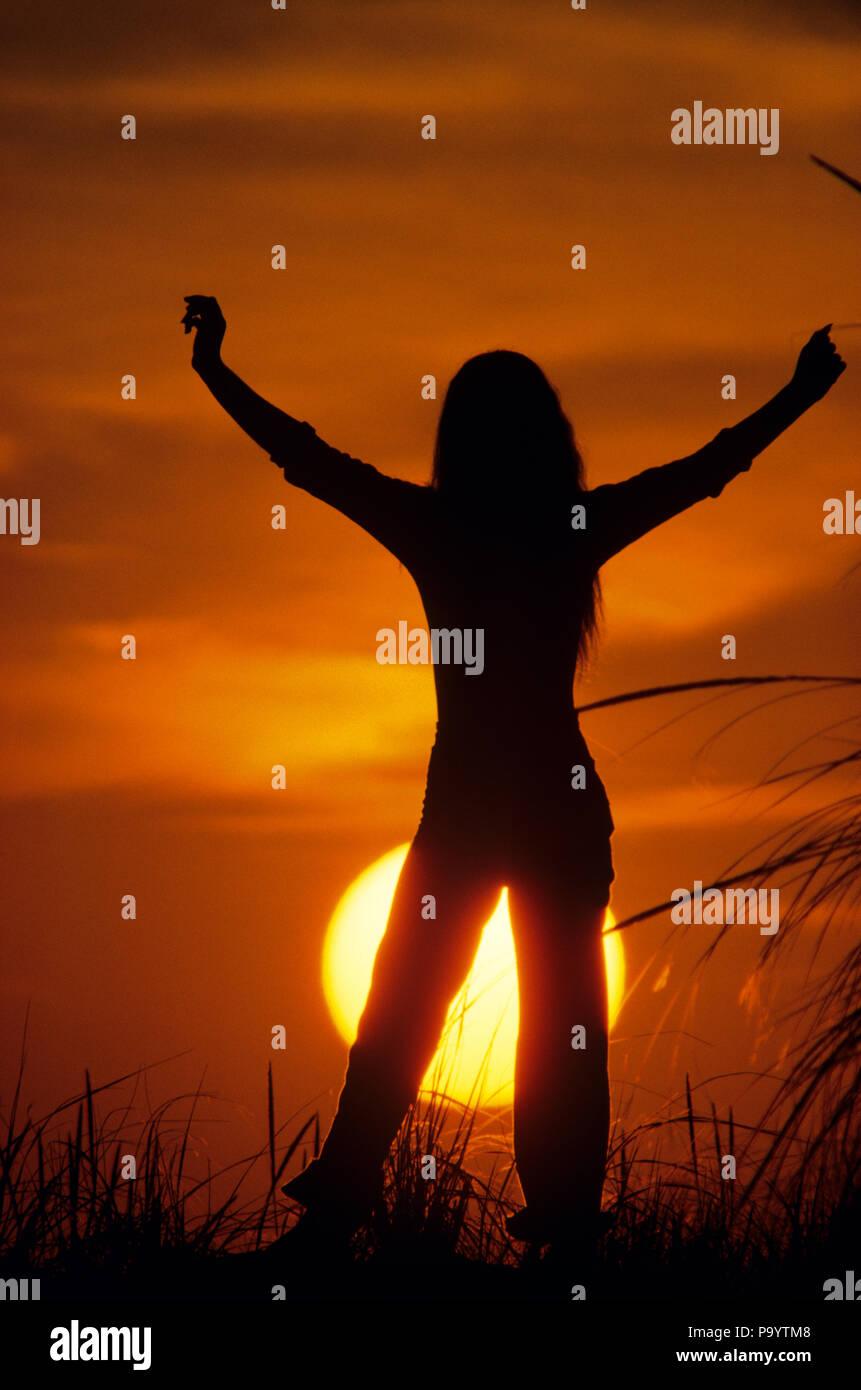 1970 JEUNE FEMME ANONYME DANS LES BRAS levés en triomphe découpé sur coucher de soleil - kg8263 KRU001 HARS JOIE DE VIE LES FEMMES RURALES CLOUD pleine longueur de la santé CHERS PERSONNES DE CONDITION PHYSIQUE D'INSPIRATION DU SOLEIL ADOLESCENTE SPIRITUALITÉ ENSOLEILLÉE LIBERTÉ CONFIANCE SUCCÈS BONHEUR SOLEIL DÉCOUVERTE AVENTURE FORCE LOISIRS SILHOUETTÉ EXCITATION CHOIX CONCEPTUEL RECONNAISSANT TENDUE GRATITUDE SOLEIL CHEVEUX LONGS BRAS TENDUS DE MAUVAISES HERBES ANONYME ADOLESCENTS DÉTENTE RESTE Jeune adulte Jeune femme début old fashioned Photo Stock