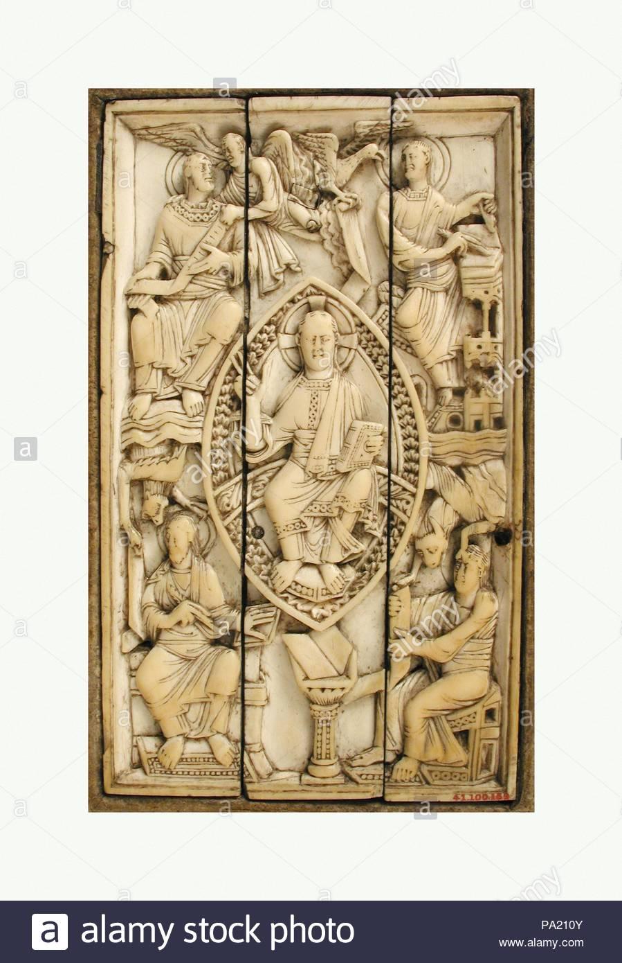 Plaque avec le Christ en majesté et les quatre évangélistes, 11e siècle, à Cologne, en Allemagne, l'ivoire, Ottonienne, Total: 6 1/8 x 3 3/4 in. (15,6 x 9,5 cm), des ivoires, les évangélistes écrivent leurs Évangiles ici avec l'aide de leurs symboles caractéristique. Un boeuf ouvert littéralement les yeux de Luc pour recevoir l'inspiration divine, alors que Mark's lion semble être la parole à l'auteur. Photo Stock