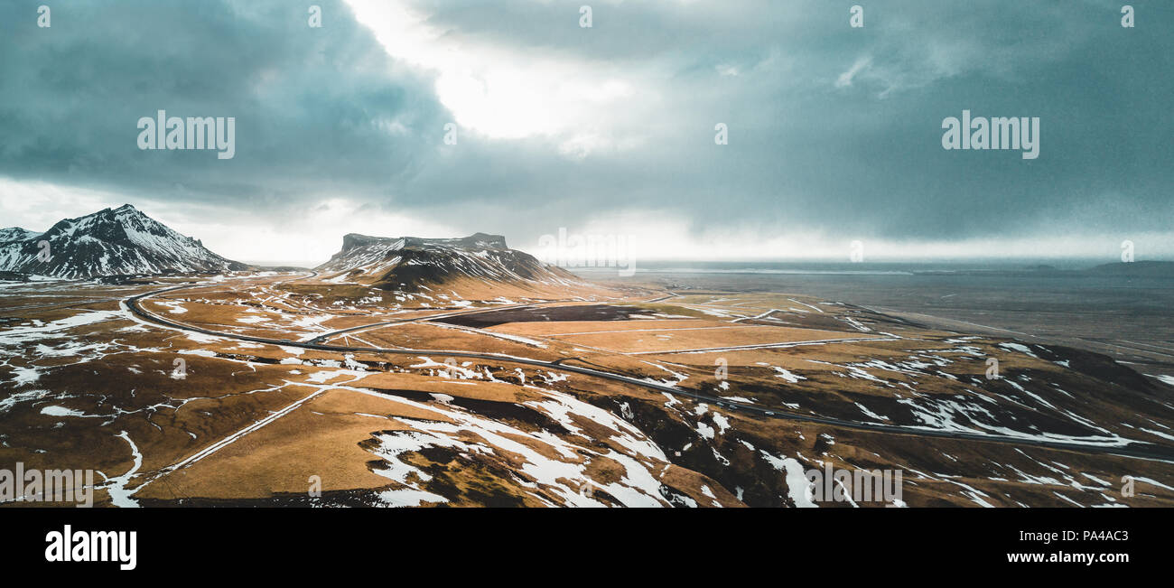 L'Islande vue aérienne paysage avec la neige et les nuages, et de la rue de l'herbe verte et jaune Photo Stock