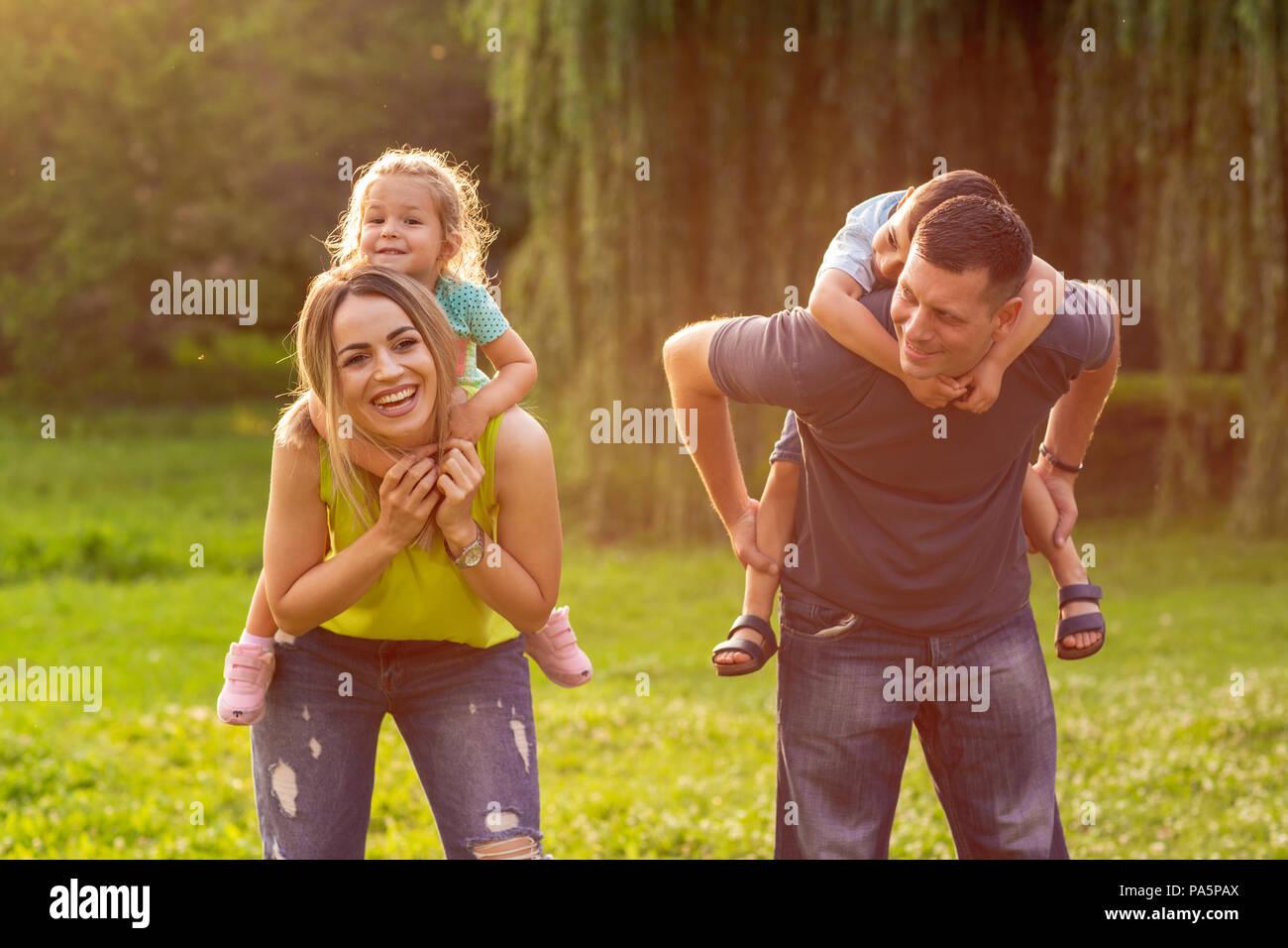 Famille heureuse piggyback leurs enfants et s'amuser ensemble dans park Banque D'Images