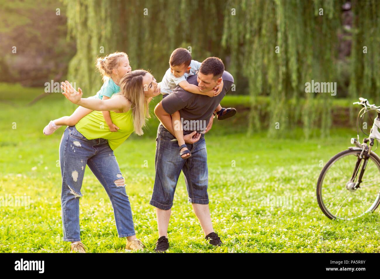 - Ferroutage famille Smiling young parents jouer avec leurs enfants dans le parc Photo Stock