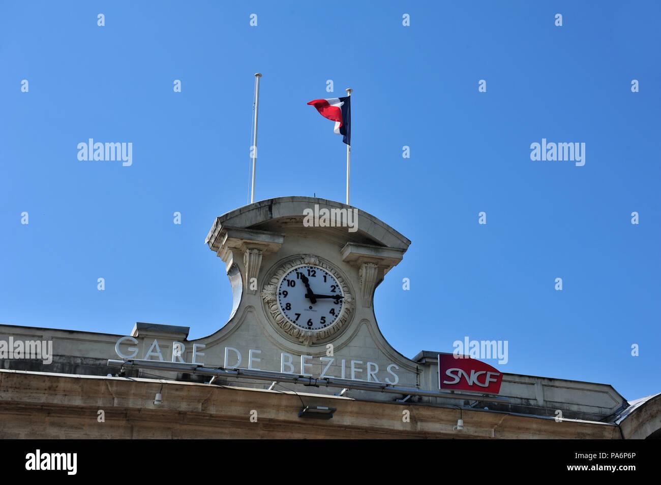 Les voyageurs français et les passagers voir cette horloge sur la façade avant de la gare de Béziers, France Photo Stock