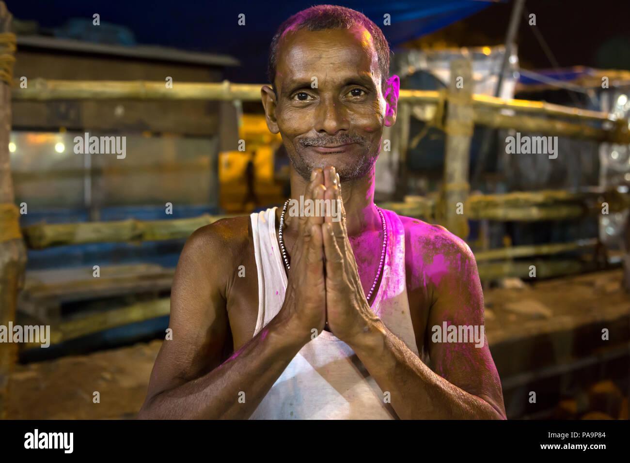 L'homme hindou de joindre les mains pendant la nuit célébration Durga puja à Calcutta, Inde Photo Stock
