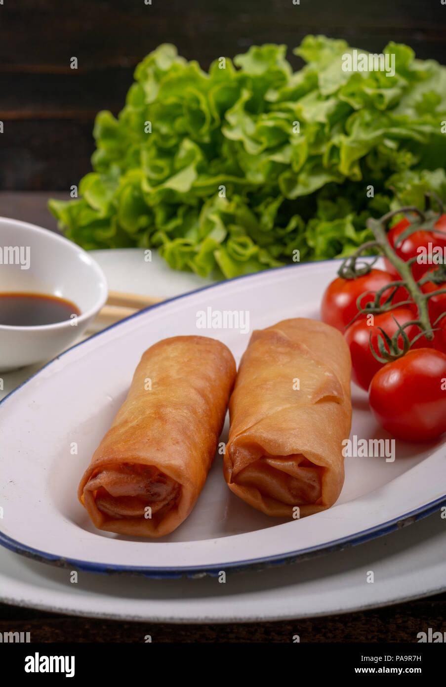 Des rouleaux de printemps accompagnés de la sauce de soja et la laitue, tomates cerise sur fond de bois Photo Stock