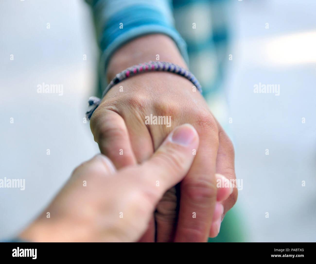 Mom's hand holding les doigts de son fils à l'extérieur Photo Stock
