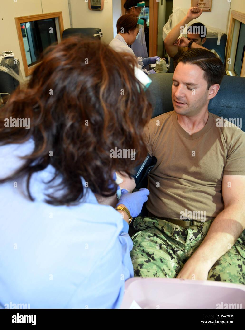 160310-N-AV746-063 CORONADO, Californie, (10 mars 2016), spécialiste de la communication de masse 1re classe Frank Andrews, attribué à le commandement des opérations spéciales de la marine, fait un don de sang pendant une collecte de sang organisée par NMCSD sur Naval Base Coronado. NMCSD travaille sur la sensibilisation sur la nécessité pour les dons de sang et relève le défi en mettant en place des collectes de sang à la Marine et du Corps des installations partout dans San Diego. (U.S. Photo par marine Spécialiste de la communication de masse 2e classe Timothy M. Black/libéré) Photo Stock