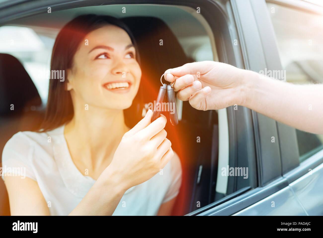 Smiling young driver se premières clés Photo Stock