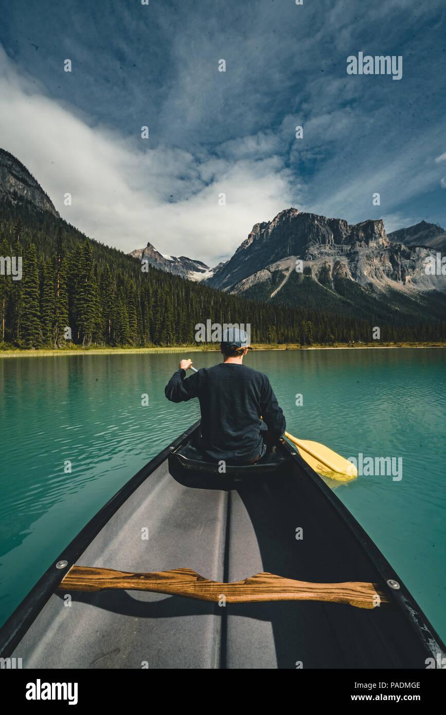 Jeune homme canoë sur le lac Emerald dans les montagnes Rocheuses du Canada avec canoë et montagnes en arrière-plan d'eau bleue. Photo Stock