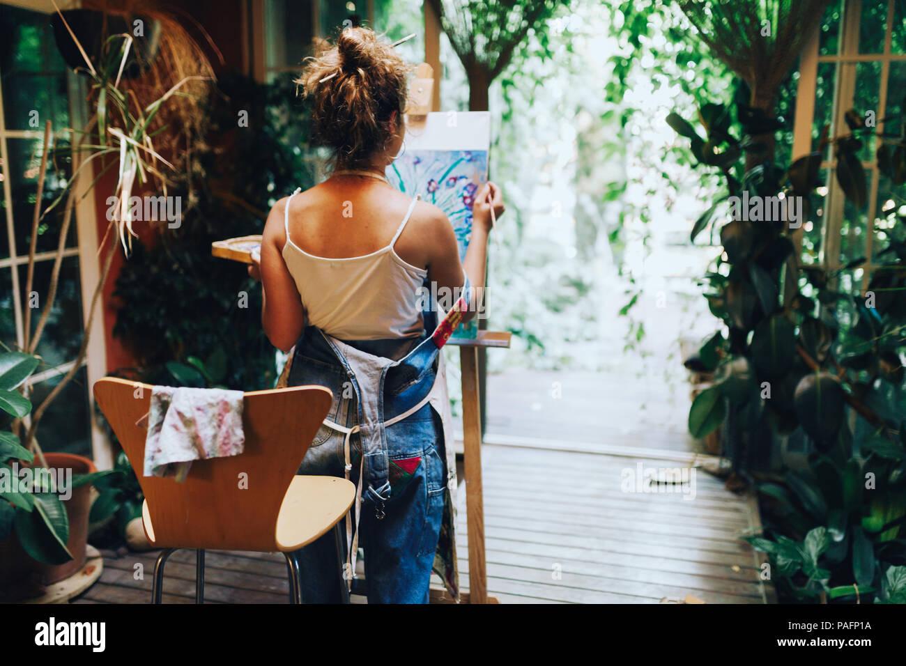 Tourné à l'intérieur de l'artiste féminin professionnel peinture sur toile en studio avec des plantes. Photo Stock