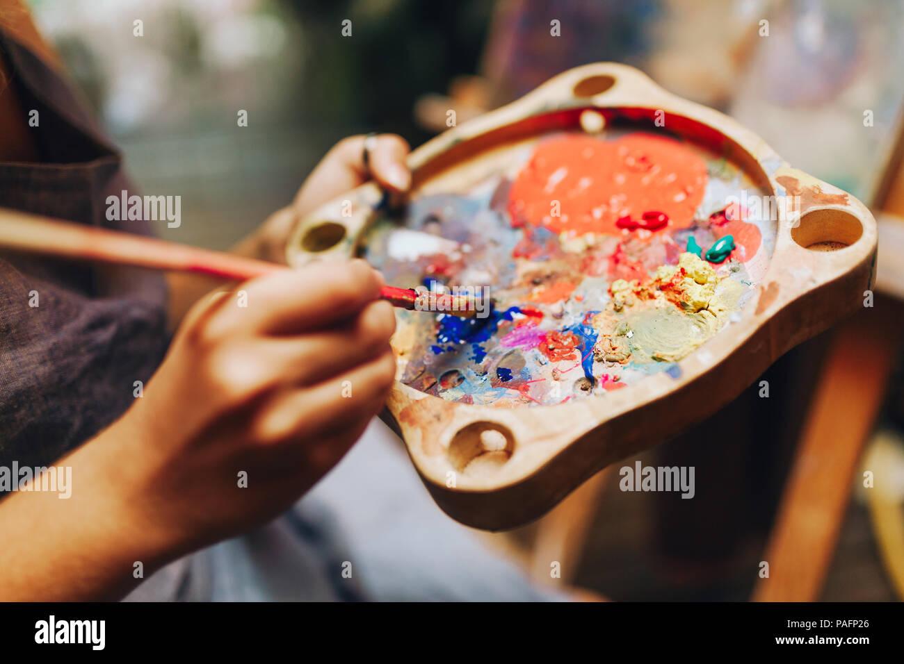 Gros plan du pinceau à mains femme mélange des peintures sur palette Photo Stock