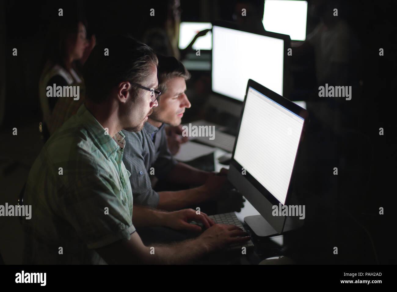 L'équipe d'affaires fonctionne sur ordinateurs le soir. Photo Stock