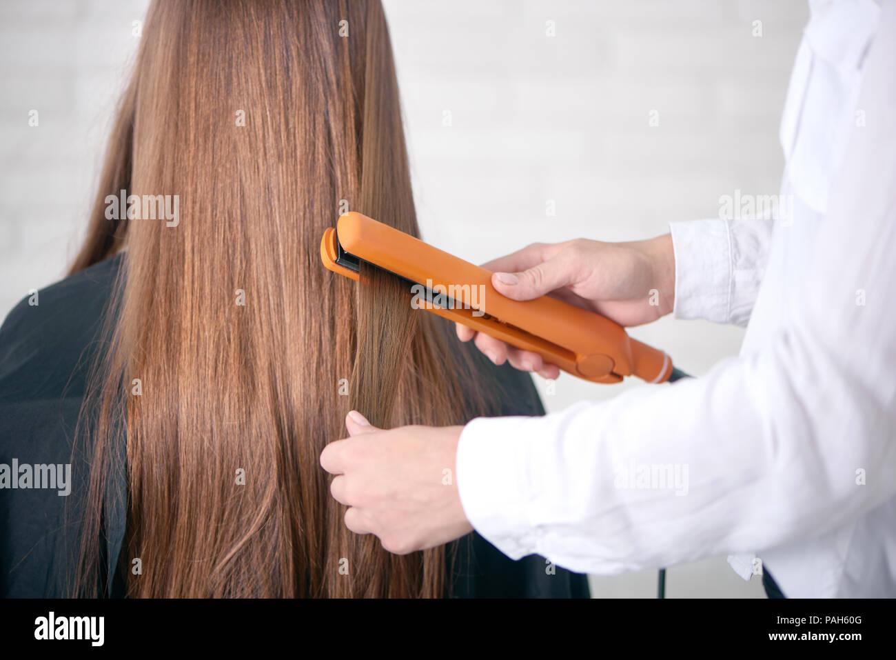 Vue arrière de coiffure straighting longs cheveux bruns du client. Modèle avoir lisse, droit, glancy, la santé des cheveux, assise recouverte d'une cape noire. Hairstyler wearing white shirt classique. Photo Stock