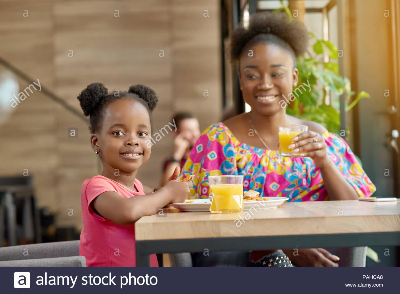 Happy smiling mother and daughter drinking orange juice, manger des pizzas. Avoir la bonne humeur, merveilleux temps ensemble, belle famille. Les autres clients assis dans le café. Intérieur Loft. Photo Stock