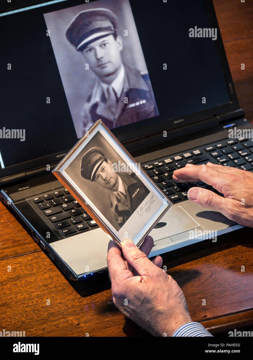 Hand holding old 1940 sépia photographie d'un officier de l'Armée britannique en uniforme avec la même image numérisée sur ordinateur portable écran derrière Photo Stock
