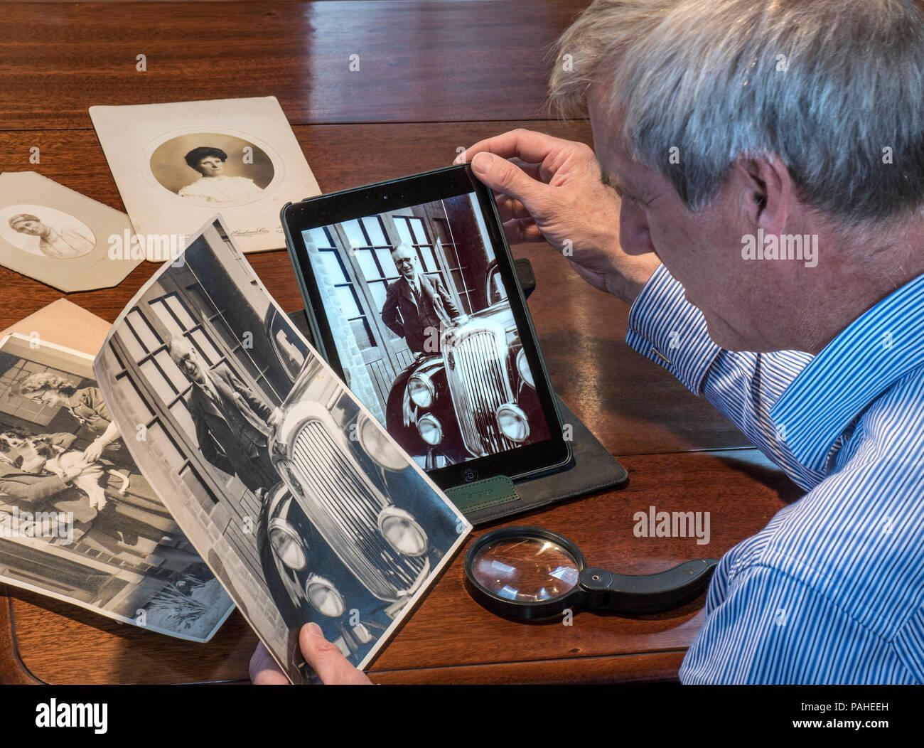Homme mûr tri par le biais de photographies anciennes compare un original B&W imprimer avec son image numérisée sur son ordinateur tablette Photo Stock