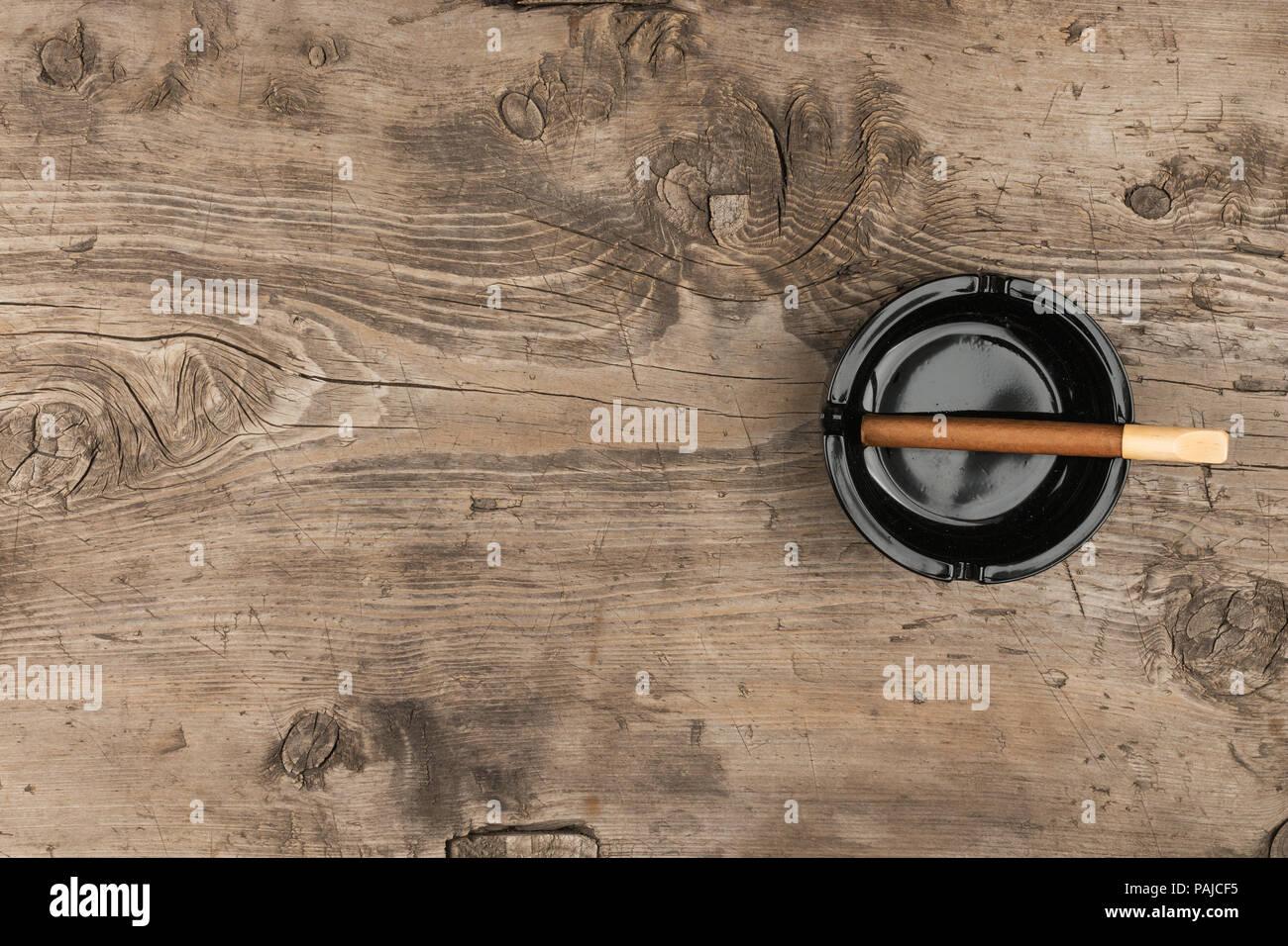 Cigare dans un cendrier sur un vieux bureau en bois avec une place