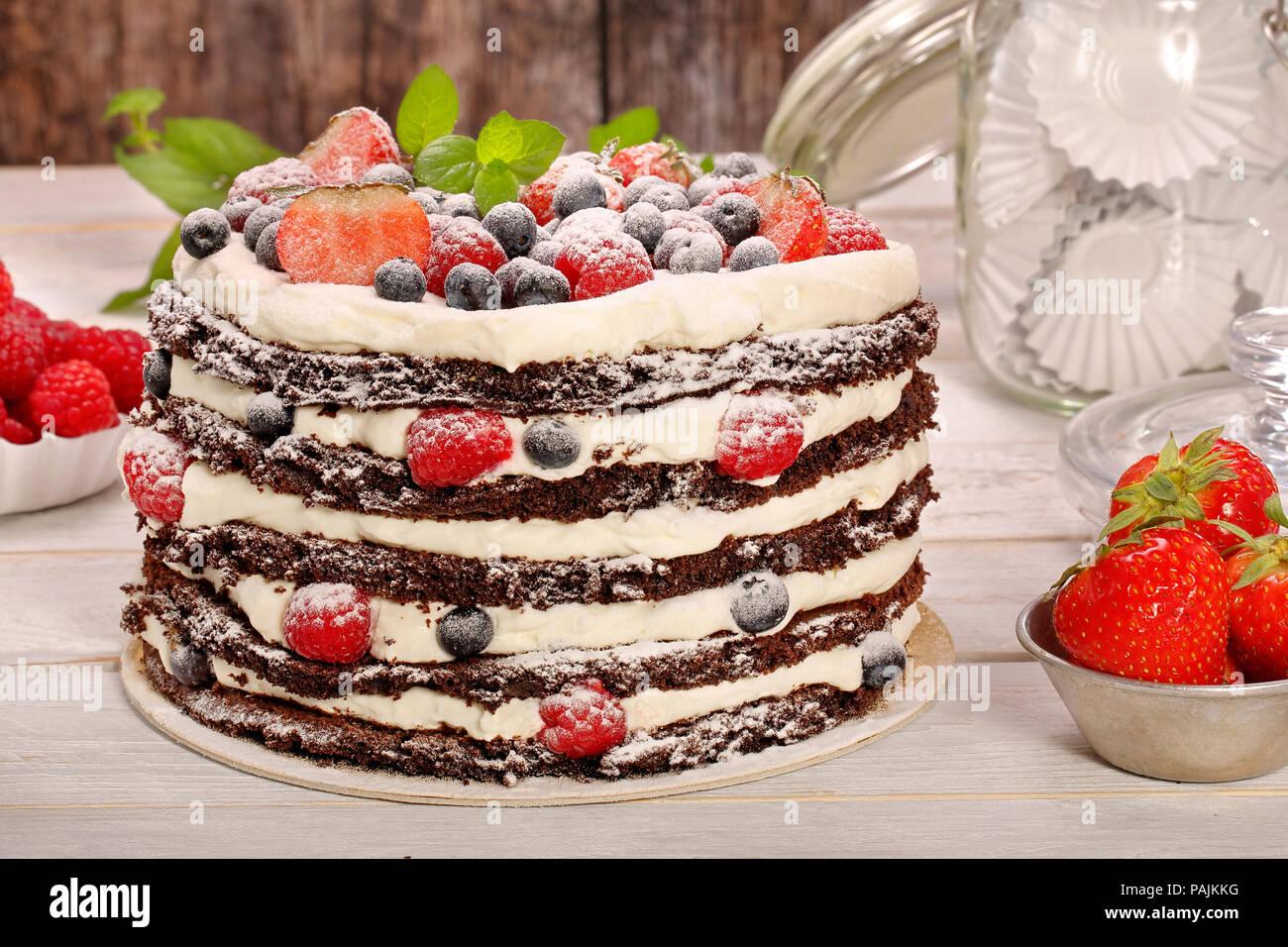 Gâteau au chocolat avec crème blanche et fruits sur fond de bois Photo Stock