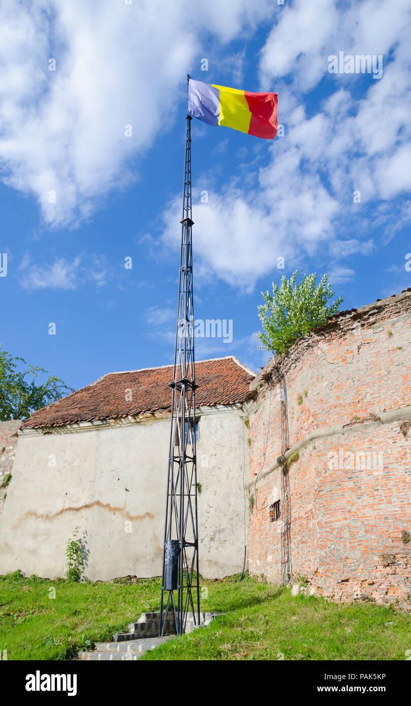 Drapeau roumain dans le vent sur fond bleu ciel nuageux à la forteresse médiévale de Brasov, avec un imposant regard respectueux Banque D'Images