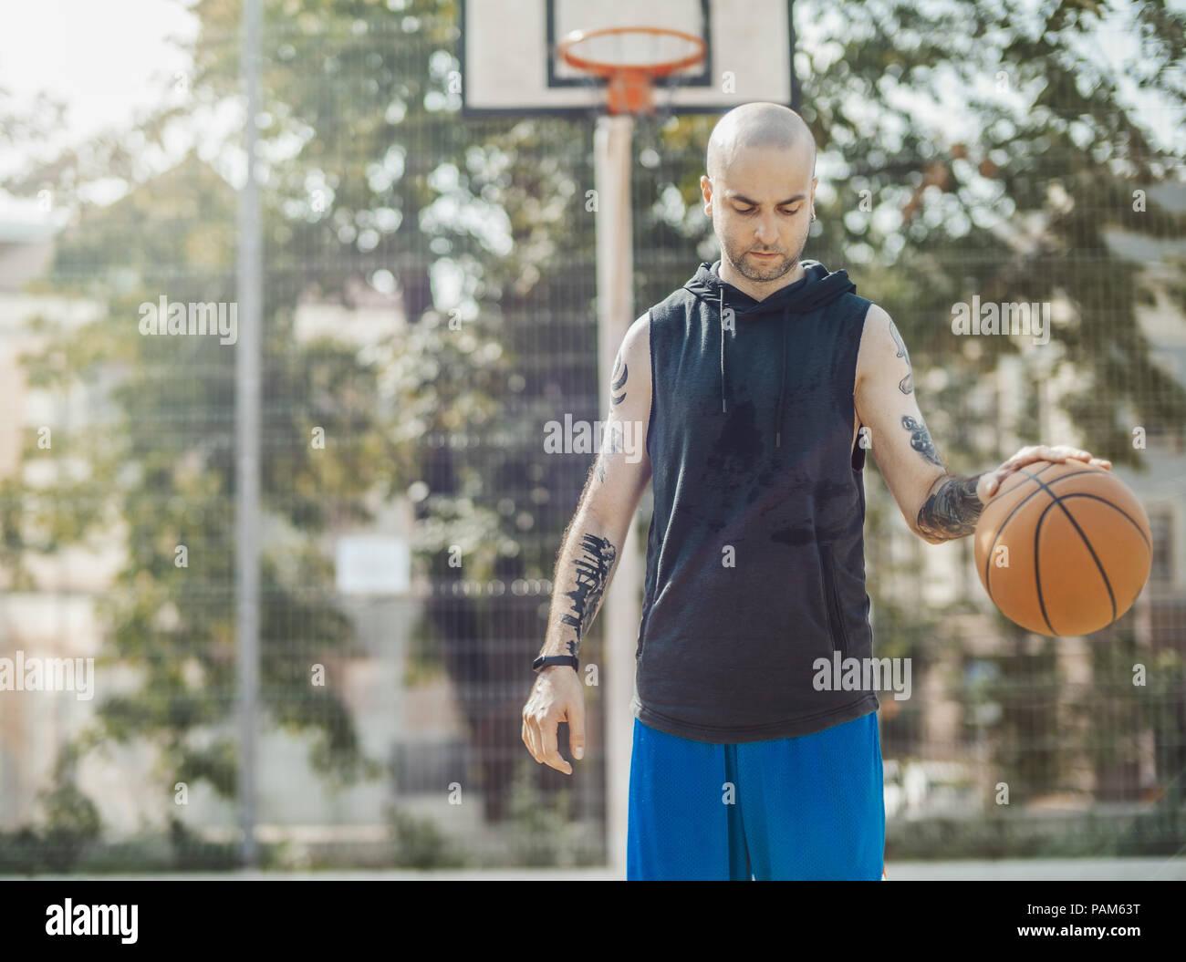 Bald woman jouer au basket-ball sur le terrain de basket-ball. L'homme est sur le point de mire et de premier plan, arrière-plan est flou. Photo Stock