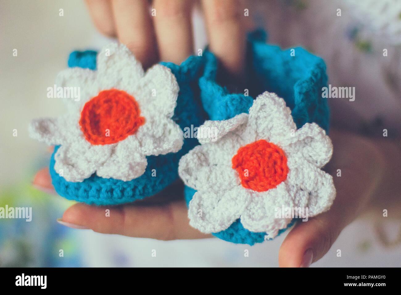 Tricots bébé chaussons en mains Photo Stock