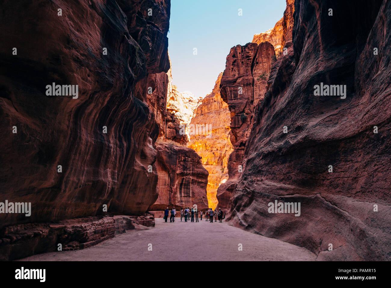 Un groupe touristique parcourt le chemin principal en Petra, Jordanie. Le canyon a été sculpté par le fractionnement du rock lors d'un tremblement de terre Photo Stock