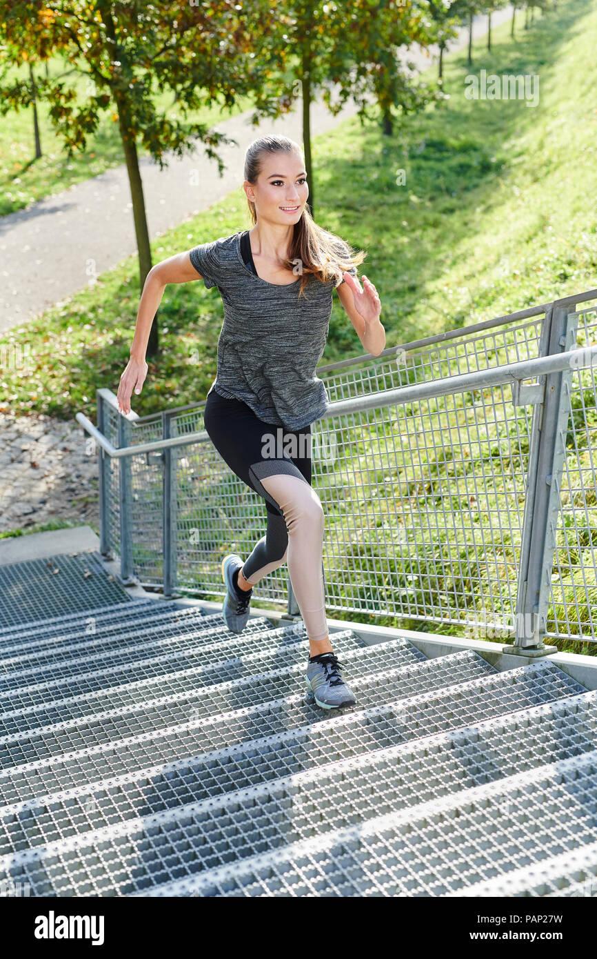 Jeune femme tournant sur des escaliers dans un parc Photo Stock