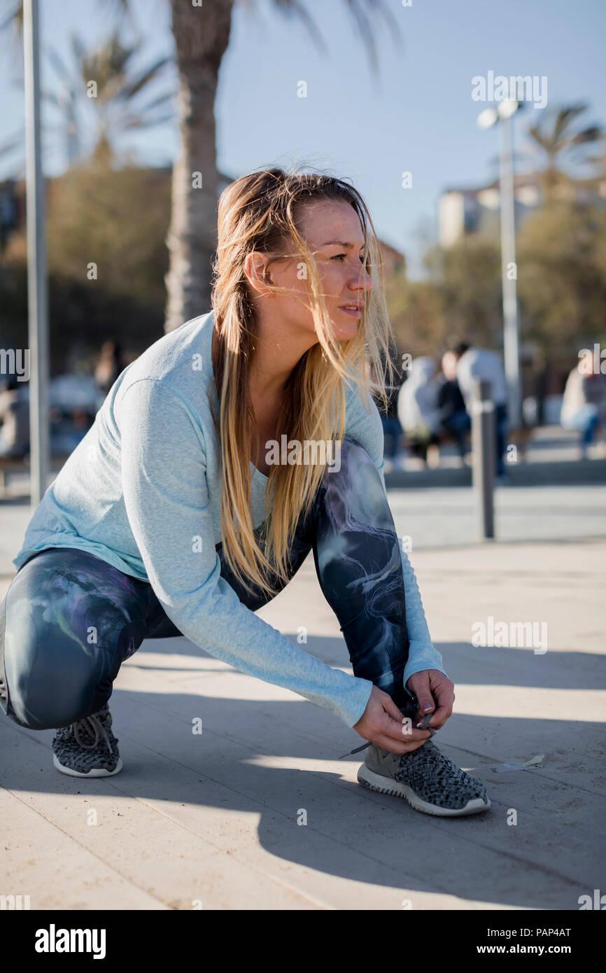 Espagne, Barcelone, chaussure de course femme attachant sur la promenade de bord de mer Photo Stock