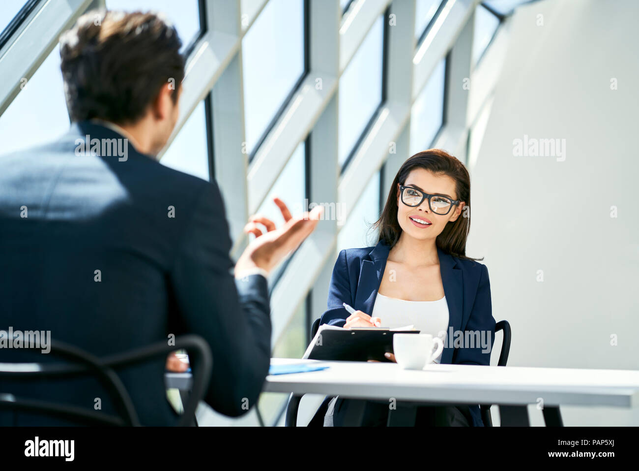 Young talking at desk in modern office Photo Stock