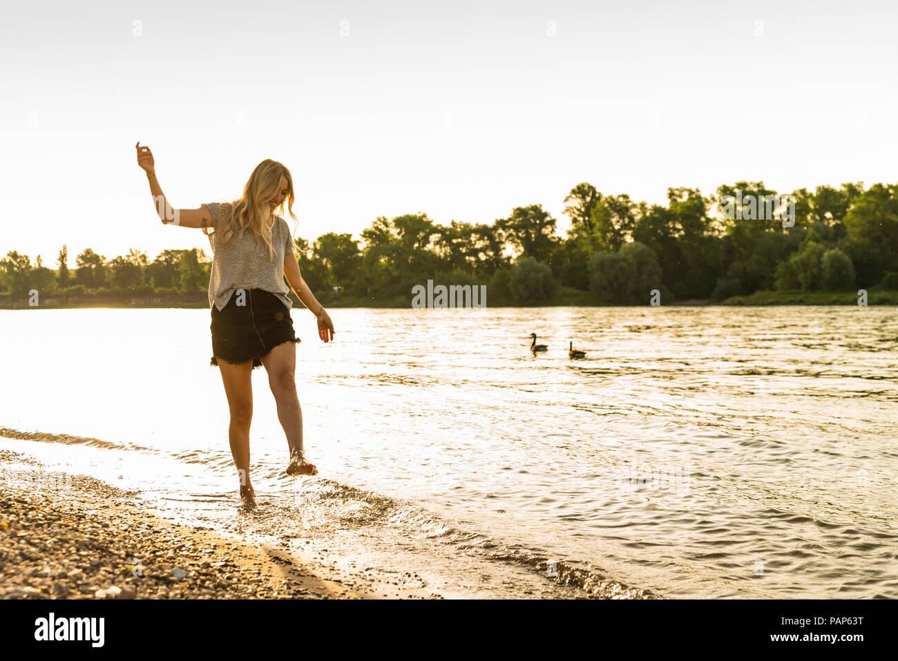 Jeune femme marchant pieds nus sur Riverside Photo Stock