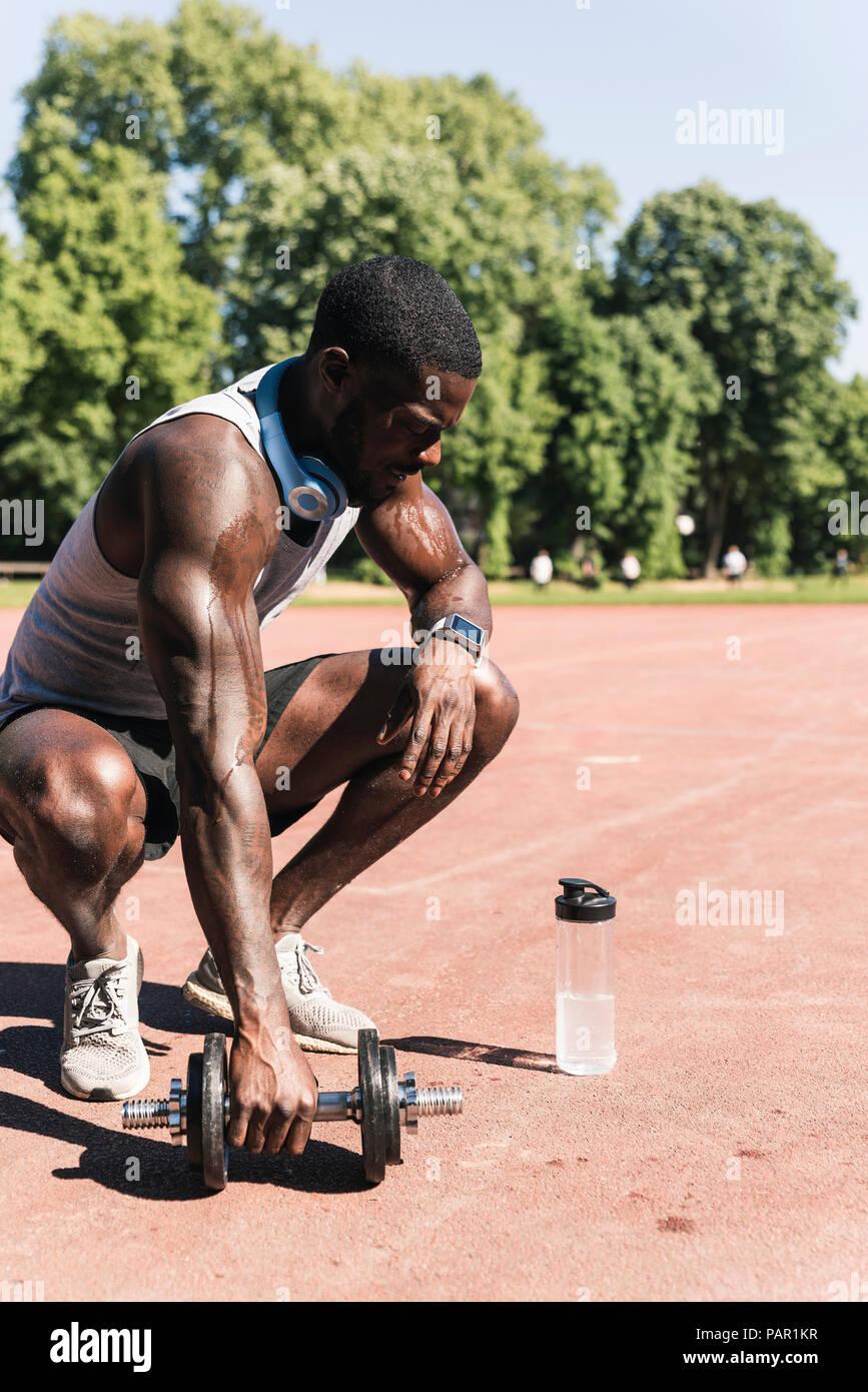 Jeune athlète faisant la formation de poids avec haltères courtes sur terrain de sport Photo Stock