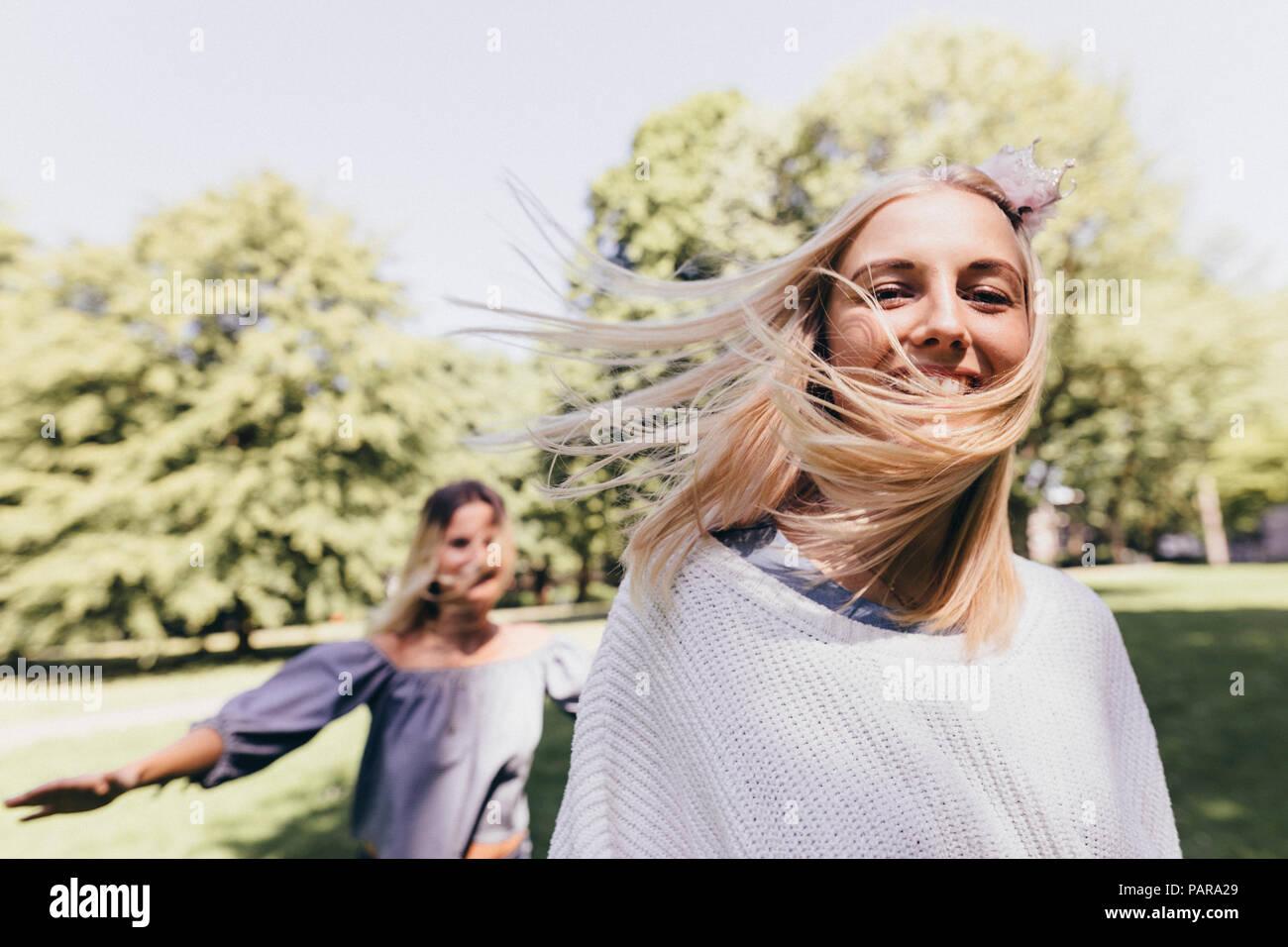 Portrait de deux jeunes femmes heureux d'exécution dans un parc Photo Stock