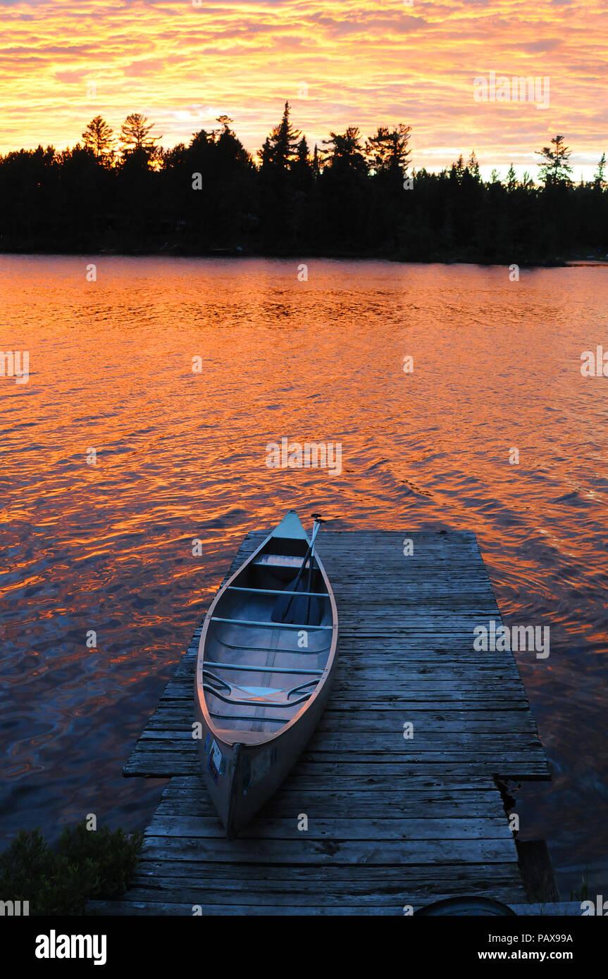 Canoë sur dock au coucher du soleil lever du soleil sur un lac dans la Boundary Waters Canoe Area près de Ely Minnesota Banque D'Images